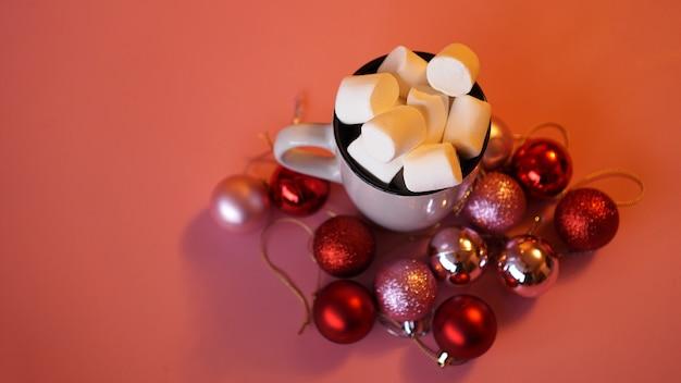 Modne świąteczne tło z gorącej czekolady z pianką marshmallow, ozdobione kulkami na różowo - widok z góry
