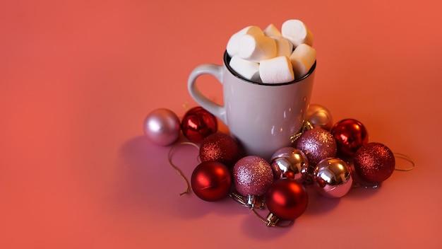 Modne świąteczne tło z gorącej czekolady z pianką marshmallow, ozdobione kulkami na różowo