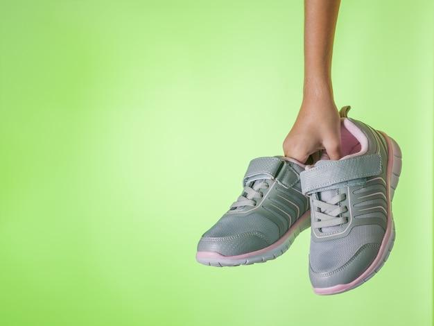Modne szare trampki w dziecięcej dłoni na zielonym tle. buty sportowe. trend kolorystyczny. miejsce na twój tekst.