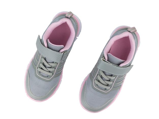 Modne szare trampki z czerwoną obwódką na białym tle. nowoczesne buty sportowe. widok z góry.