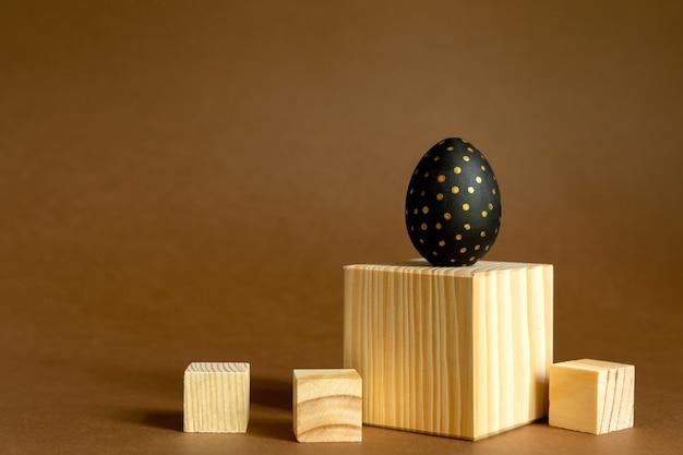 Modne tło wielkanocne. złote i czarne malowane jajka stoją na drewnianych kostkach, podium na brązowym tle.
