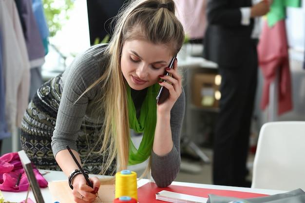 Modne ubrania na zamówienie talking phone designer. zajęty młoda kobieta z smartphone. krawcowa kaukaska tworzenie szkicu. koncepcja biznesowa robótki ręczne. inspirujące biuro nowoczesnego stylisty