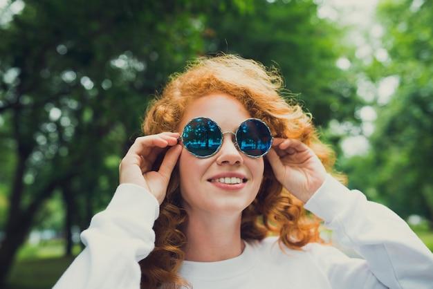 Modne włosy rudy młoda kobieta w okularach przeciwsłonecznych