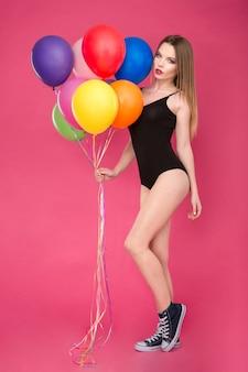 Modne zdjęcie pięknej uwodzicielskiej, atrakcyjnej młodej kobiety w czarnym stroju kąpielowym z kolorowymi balonami
