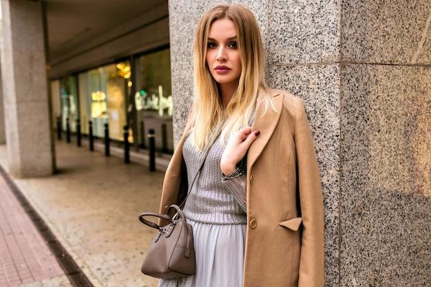 Modne zdjęcie w stylu ulicznym przedstawiające elegancką blondynkę, ubrana w luksusową jedwabną sukienkę, modny sweter, kaszmirowy płaszcz i skórzaną torbę, miękkie ciepłe kolory, wiosenno-jesienny nastrój w środku sezonu.