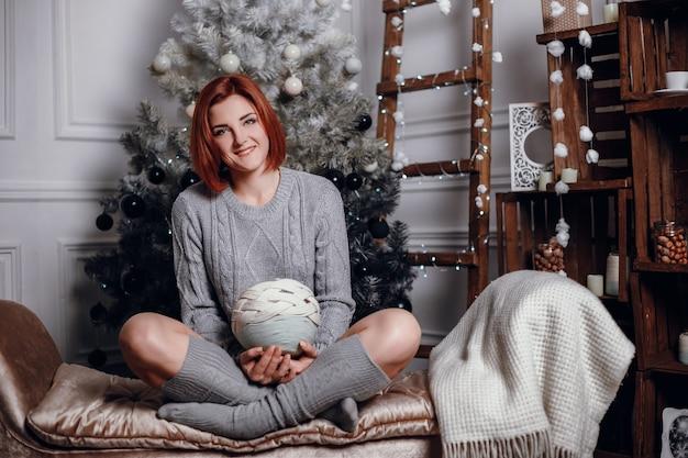 Modne zdjęcie wewnętrzne pięknej młodej kobiety z czerwonymi włosami i uroczym uśmiechem, nosi przytulny sweter z dzianiny, pozuje obok choinki i przedstawia ciasto czekoladowe z gwiazdkami