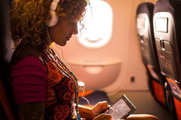 Modni podróżnicy i piękna kaukaska kobieta słuchają muzyki lub pracują w samolocie