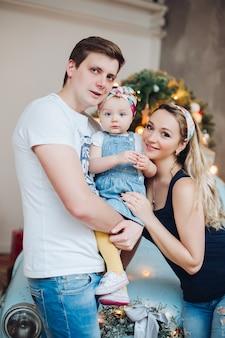 Modni rodzice trzyma dalej małą śliczną córkę, stoi blisko błękitnego retro samochodu.