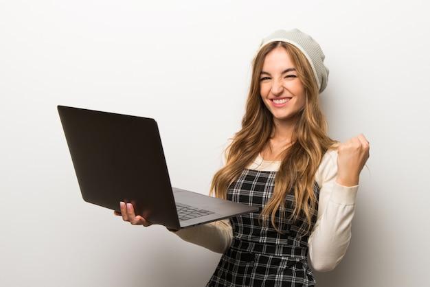 Modnie kobieta ma na sobie kapelusz z laptopem i świętuje zwycięstwo