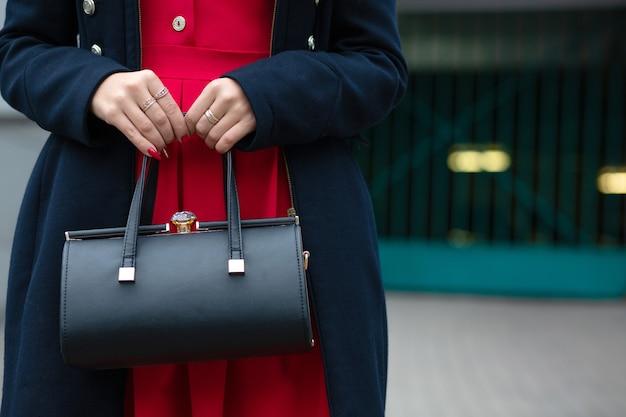 Modnie ubrana dziewczyna trzyma czarną skórzaną torebkę. pusta przestrzeń