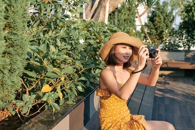 Modnie ubrana kobieta siedzi w parku i używa aparatu