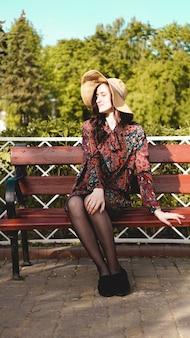 Modnie ubrana młoda ładna kobieta na ulicy w słoneczny dzień. piękna dziewczyna w sukience i kapeluszu siedzi na ławce i uśmiecha się. koncepcja mody ulicznej
