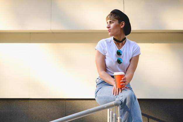 Modniś dziewczyna pije kawę iść