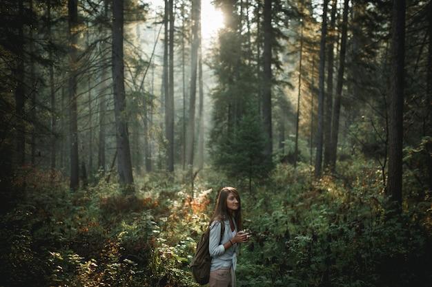 Modniś dziewczyny mienia kubek w lesie