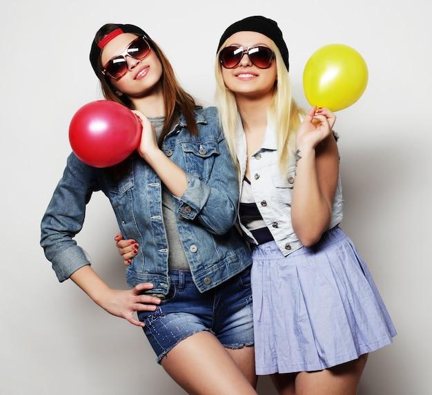 Modniś dziewczyny uśmiecha się kolorowych balony i trzyma