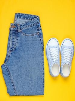 Modniś kobiet sneakers z niebieskimi dżinsami na żółtym tle. widok z góry, leżał płasko, minimalizm