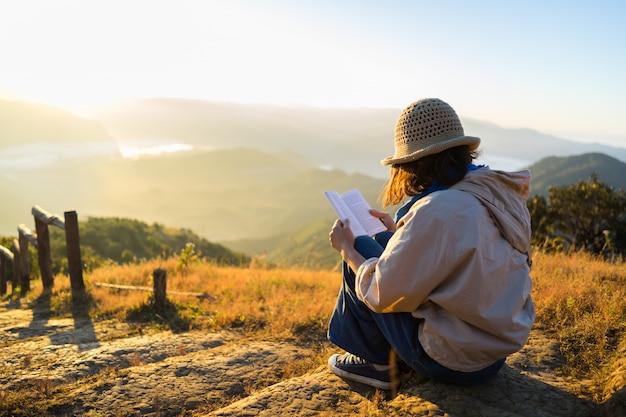 Modniś kobieta czyta książkę przy pięknym wschodem słońca nad górami.