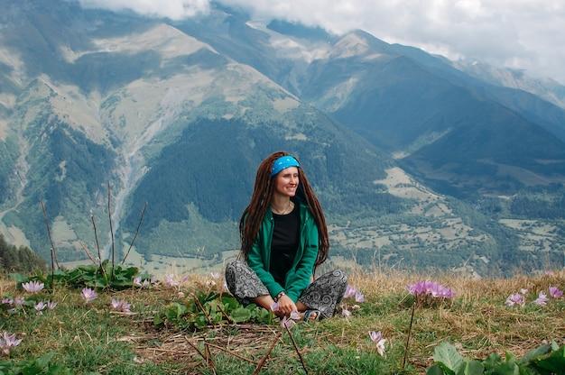 Modniś kobieta siedzi na górze z dreadlocks