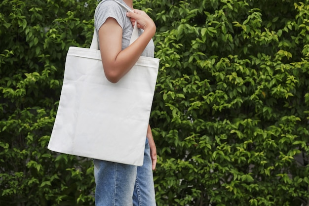 Modniś kobieta z białą bawełnianą torbą na zielonym liścia tle