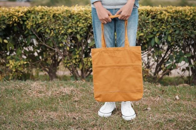 Modniś kobieta z żółtą dużego ciężaru torbą na zielonej trawy tle