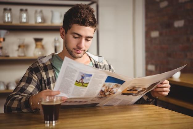 Modniś ma kawę i czytelniczą gazetę przy sklep z kawą