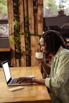 Modniś pije filiżankę kawy podczas gdy używać laptop
