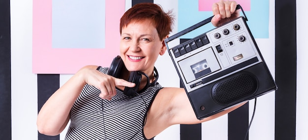 Modniś starsza kobieta pokazuje rocznik kasety gracza