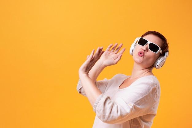 Modniś starsza kobieta tanczy muzykę i słucha
