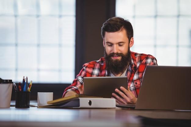 Modniś używa cyfrową pastylkę przy biurkiem