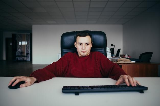 Modnisia młody człowiek pracuje w biurze przy komputerem. dokładnie spójrz na kamerę