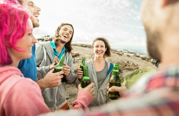 Modnisiów przyjaciele ma zabawę wpólnie przy plażowym campingowym przyjęciem