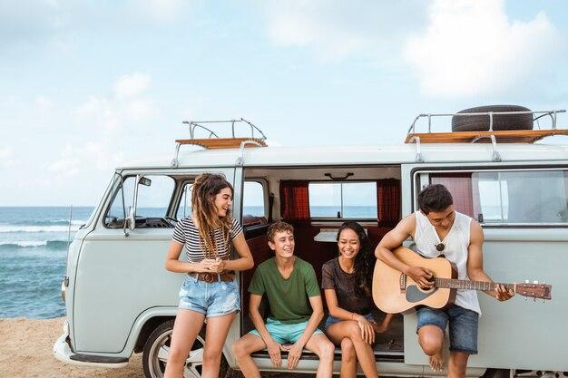 Modnisiów przyjaciele w retro samochodzie dostawczym przy plażą