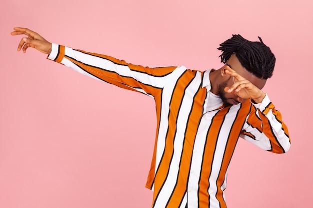 Modny afroamerykanin wykonujący ruch taneczny dab, naśladujący słynny internetowy mem, wyrażając triumf