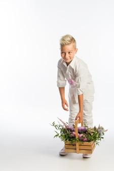 Modny blond chłopiec z drewnianym koszem kwiatów