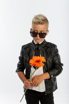 Modny blond chłopiec z pojedynczym kwiatem gerbera