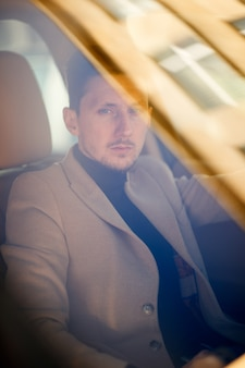 Modny bogaty kaukaski mężczyzna siedzi w nowym nowoczesnym samochodzie i poważnie patrzy prosto przez przednią szybę