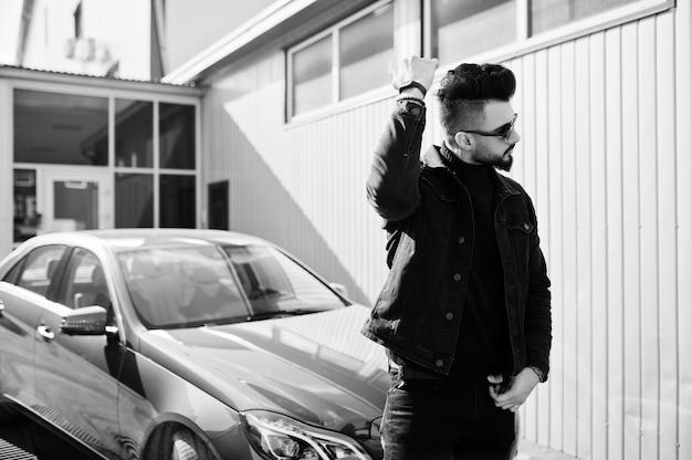 Modny brodaty młody człowiek pozuje outdoors z dużym samochodem