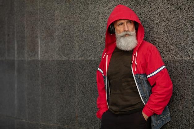 Modny brodaty starszy mężczyzna słucha muzyki na wolnym powietrzu. moda dojrzały mężczyzna.