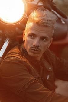 Modny brutalny przystojny mężczyzna z fryzurą w khaki kurtce siedzi wieczorem w pobliżu motocykla ze światłem na ulicy