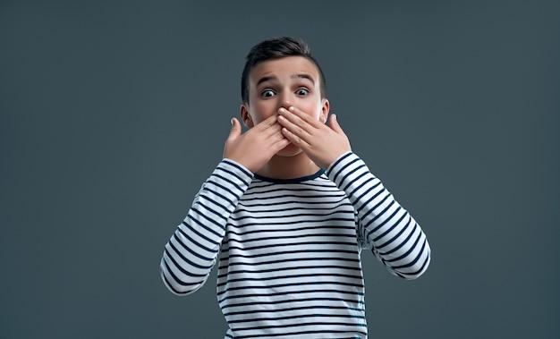 Modny chłopak zakrywający usta rękami patrząc prosto przed siebie.