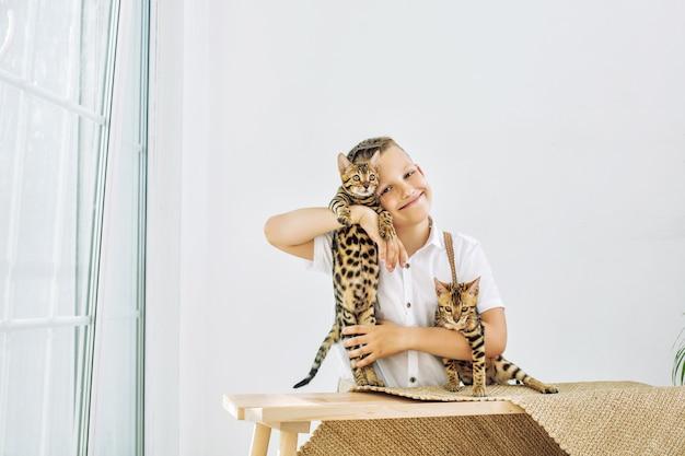 Modny chłopiec piękny i szczęśliwy z małymi uroczymi kociętami bengalskimi razem