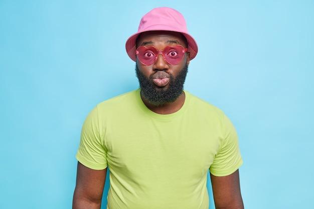 Modny ciemnoskóry facet nosi różową zieloną koszulkę panama i okulary przeciwsłoneczne w kształcie serca, które zaokrąglają usta, ma romantyczny wyraz, ubrany w letnie ciuchy