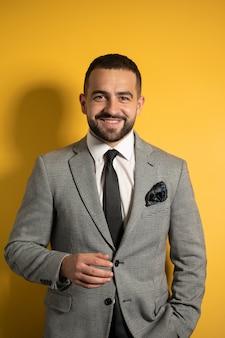 Modny czarujący facet w szarym garniturze, patrząc na ciebie ze słodkim uśmiechem z jedną ręką złożoną na żółtej ścianie