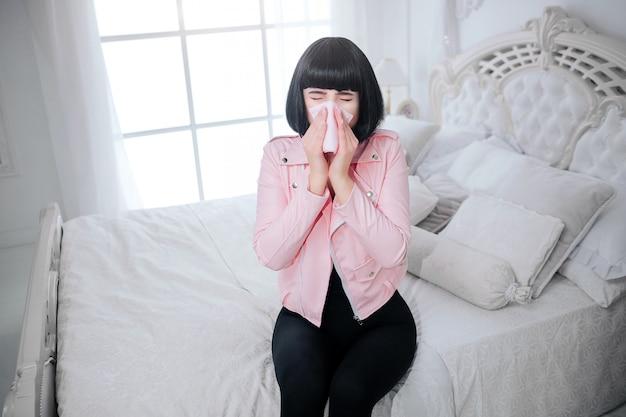 Modny dziwak. glamour kobieta z krótkimi czarnymi włosami dmucha nos i cierpi na choroby w białej sypialni. stylowa dziewczyna w różowej kurtce. koncepcja mody i opieki zdrowotnej