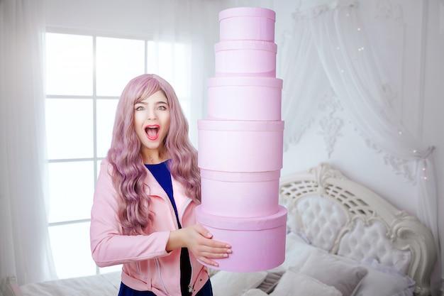 Modny dziwak. splendor szczęśliwa piękna kobieta z długim lilym włosy trzyma różowe pudełka podczas gdy stojący w białej sypialni. pojęcie piękna i mody.