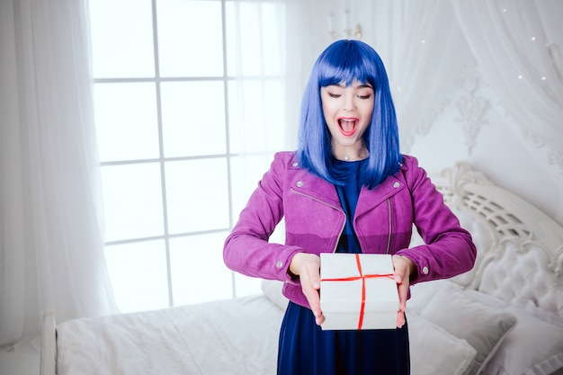 Modny dziwak. urok zaskoczył piękną kobietę o niebieskich włosach trzyma prezent w białej sypialni. koncepcja mody i urody
