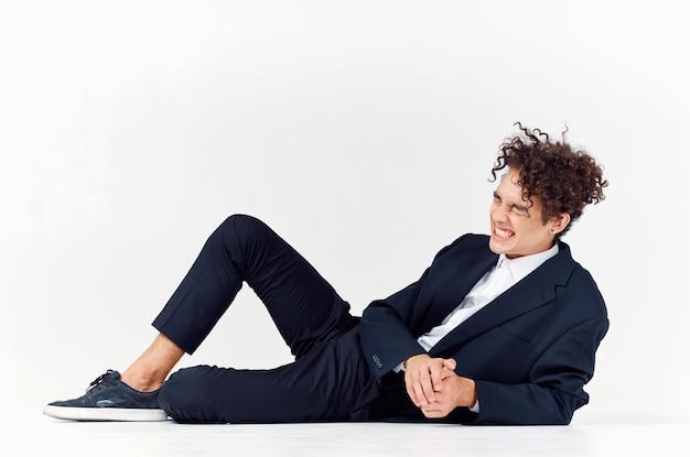 Modny facet w spodniach i kurtce leży na podłodze w jasnym pokoju w trampkach z kręconymi włosami