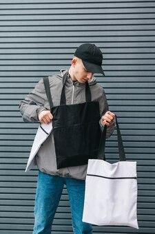 Modny facet w stylowych ubraniach z ekologicznymi torbami w rękach na szaro