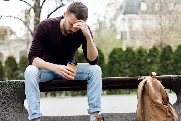 Modny facet z , spacerując po mieście z filiżanką kawy w ręku. przygnębiony facet
