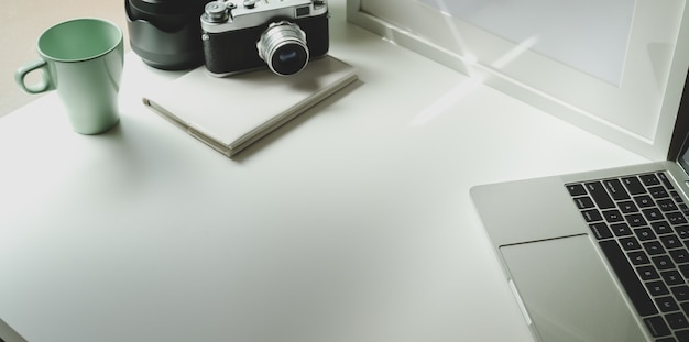 Modny fotograf pracy z tabletem i zabytkowym aparatem